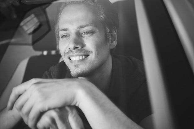 ドライブをお楽しみください。車に座っている若いハンサムな男の画像。