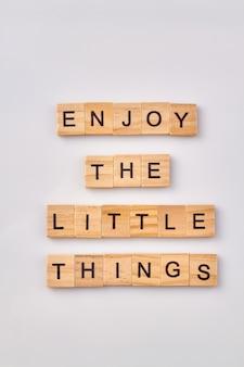 사소한 것들을 즐기다. 행복을 찾기위한 현명한 조언. 흰색 배경에 고립 된 편지와 함께 나무 큐브.
