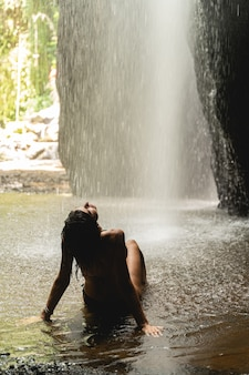 순간을 즐겨라. 소풍 중 폭포 근처에서 쉬면서 수영복을 입은 친절한 젊은 여성