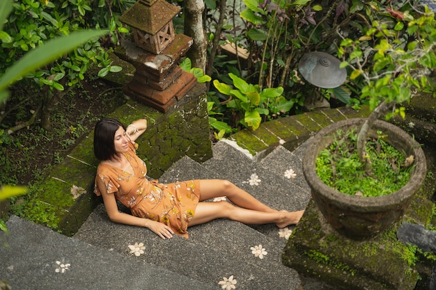 순간을 즐겨라. 자연을 혼자 명상하면서 계단에 앉아 기뻐하는 여성