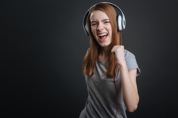 Наслаждайтесь звуком. оптимистичная и выразительная девушка слушает свои песни, тестирует новое оборудование и наслаждается им.
