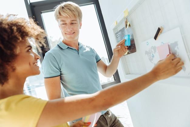 함께 일하는 것을 즐기십시오. 쾌활한 젊은 국제 동료가 웃고 사무실에 서있는 동안 작업 계획을 위해 스티커 메모를 사용하여