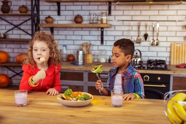 Приятного аппетита. внимательный мальчик-брюнетка сидит рядом со своим другом и смотрит на свежие овощи