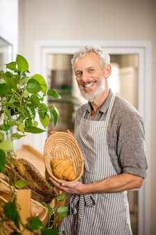 Enjoy your meal. gray-haired bearded joyful man in apron showing fresh croissant in basket standing in bakery shop