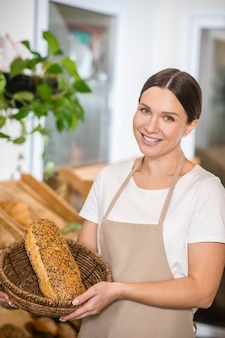 Enjoy your meal. pretty smiling dark haired woman in apron showing fresh bread in basket at bakery store