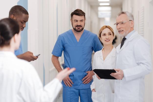同僚との楽しい時間。病院でコーヒーブレイクを楽しんで、ニュースを共有しながら喜びを表現する前向きな賢い開業医の笑顔