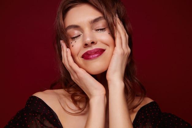 빨간 입술과 그녀의 얼굴에 작은 은색 별을 가진 즐거운 젊은 갈색 머리 예쁜 여자, 닫힌 눈으로 즐겁게 웃고, claret 배경에 포즈를 취하는 동안 제기 손으로 얼굴을 잡고