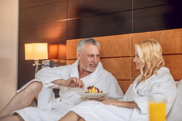 Наслаждались. жена и муж завтракают в постели и наслаждаются им