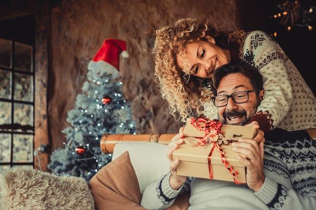 クリスマス休暇のために贈り物を交換する自宅でカップルを楽しんだ