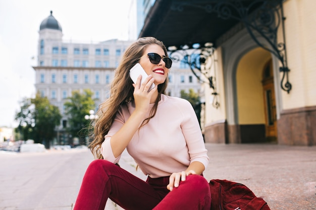 Enjoyed girl with long hairstyle is chilling on stairs in city. she wears vinous pants, speaking on phone and smiling to side.