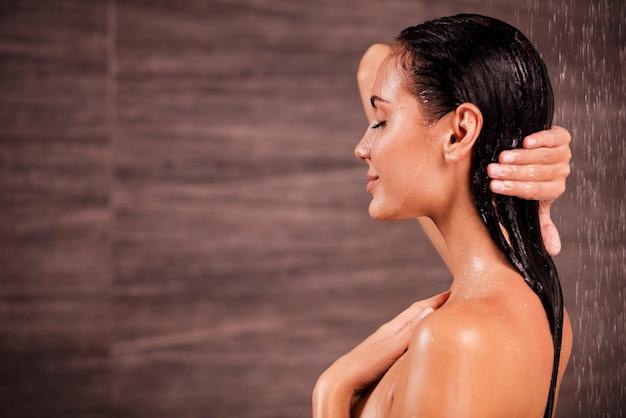 샤워를 즐기고 있습니다. 샤워를 하는 아름 다운 젊은 벗은 여자의 측면 보기