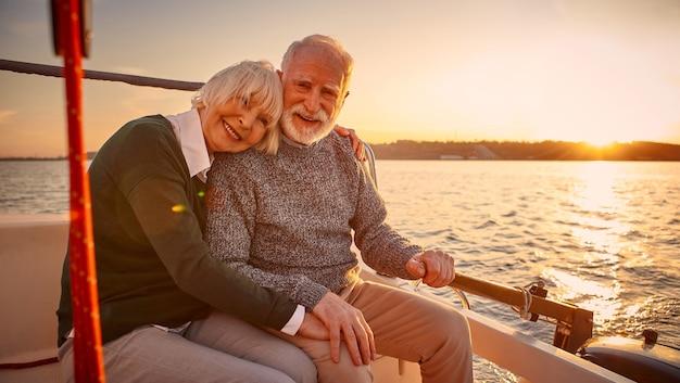 素晴らしい夕日を楽しんで幸せな年配のカップルの老人と女性が抱き合って手をつないで