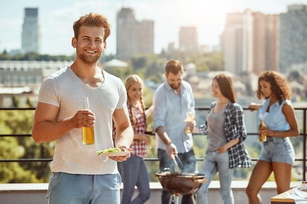 若くて陽気な男がビールとプレートのボトルを持っている友人とバーベキューを楽しんでいます
