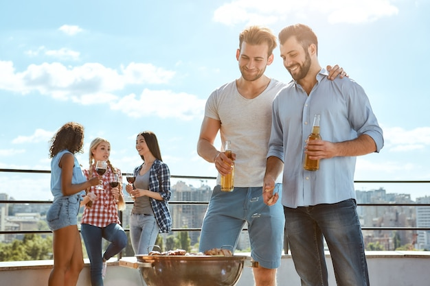 Enjoying barbeque together two smiling young men drinking beer and barbecuing meat on the grill
