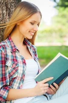 책과 신선한 공기를 즐기십시오. 공원에서 나무에 기대어 책을 읽고 웃고 있는 아름다운 젊은 여성의 측면