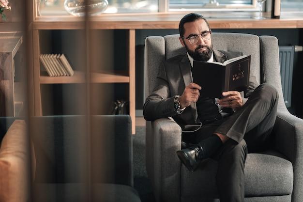 휴식을 즐기고 있습니다. 성경을 읽는 동안 직장에서 휴식을 즐기는 수염 성숙한 사업가