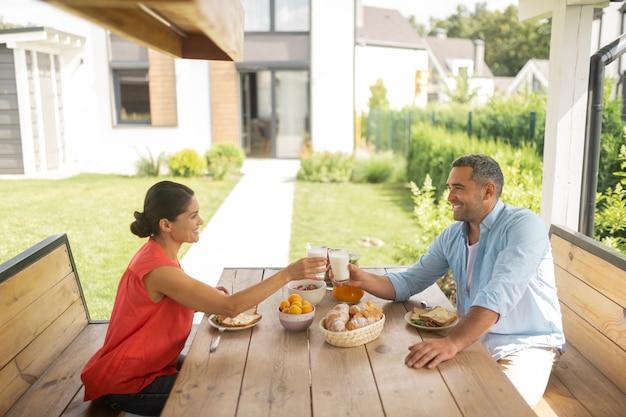 朝食を楽しんでいます。週末に外でおいしい朝食を楽しんでいるビジネスマンのカップル