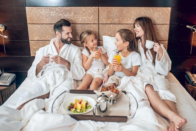 Наслаждаюсь завтраком. семья завтракает в постели и наслаждается им