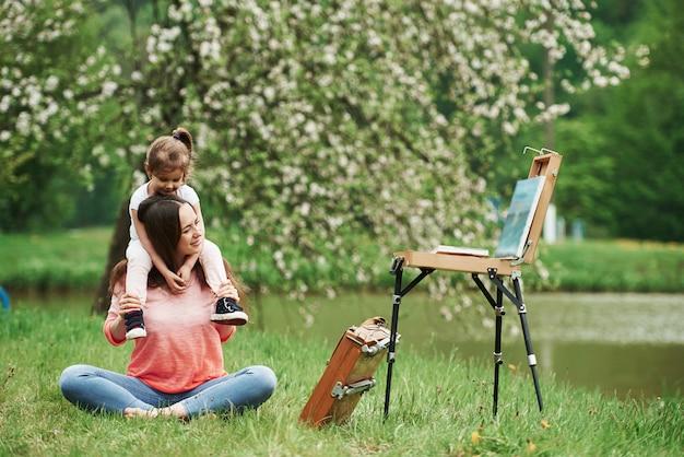 Наслаждаюсь просмотром живописи. мать и дочь сидят возле мольберта в парке весной