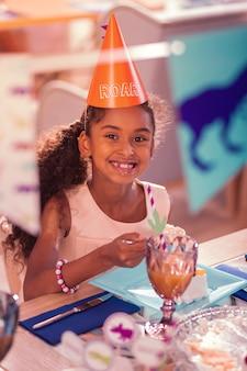 ケーキを楽しんでいます。パーティーハットをかぶって、おいしいケーキを食べながら幸せそうに笑っている陽気なリラックスした女の子