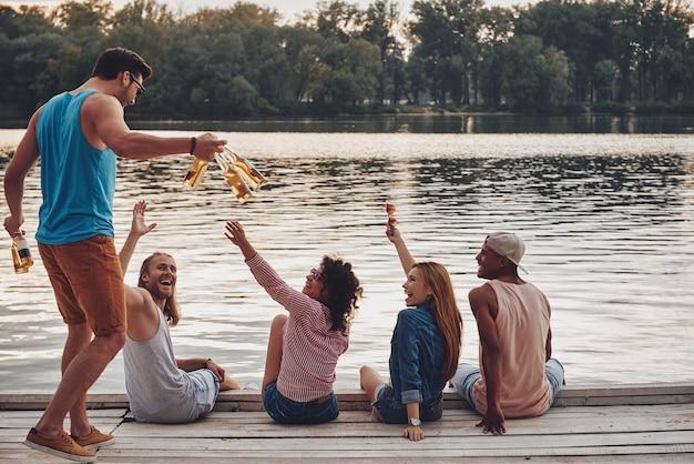 のんびりとした時間を楽しんでいます。桟橋に座って笑顔でビールを飲みながらカジュアルな服装で幸せな若者のグループ