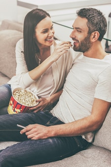 Enjoying carefree time together. beautiful young loving couple bonding to each other and eating popcorn while sitting on the couch and watching tv