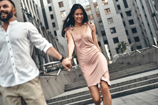 여유롭게 산책을 즐깁니다. 야외에서 계단을 내려가면서 손을 잡고 웃고 있는 아름다운 젊은 부부