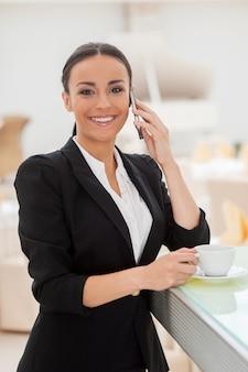 Наслаждаемся перерывом на кофе. красивая молодая женщина в формальной одежде пьет кофе и разговаривает по мобильному телефону, опираясь на барную стойку