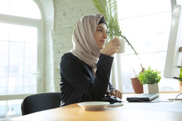 커피를 즐기는 히잡을 쓴 아름다운 아라비아 사업가의 초상화