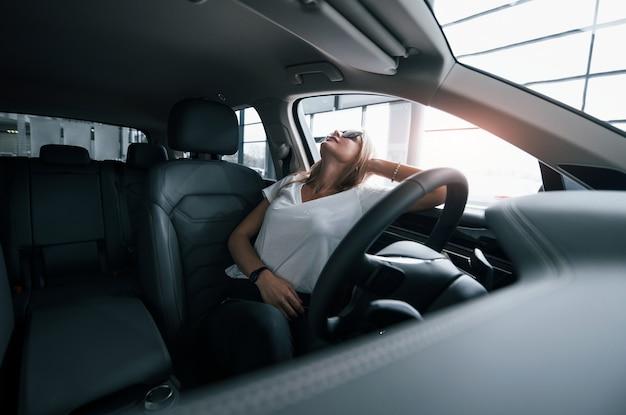 快適なインテリアを楽しんで。サロンで現代の車の女の子。昼間の屋内。新しい車を買う