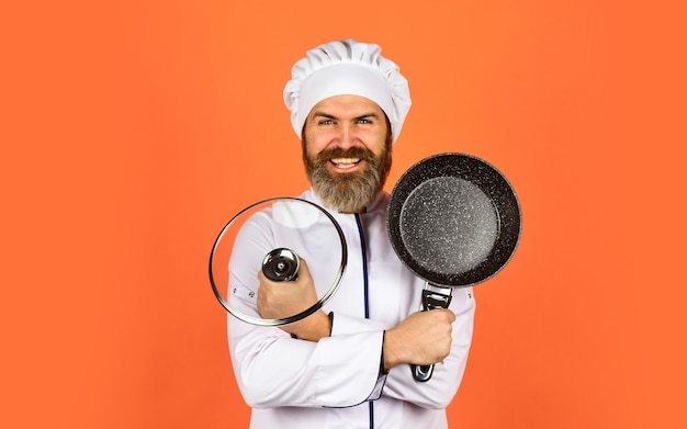 Наслаждаюсь приготовлением пищи. шеф-повар держит посуду. счастливый повар мужчина держит сковороду. шеф-повар в мундире готовит суп. кухня ресторана. готовить обед на кухне. моя профессия. пекарь с кастрюлей. общественное питание.