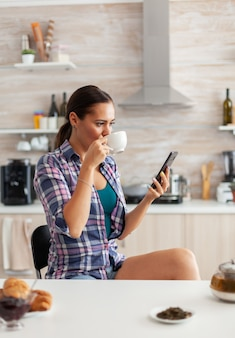 Enjoying a cup of green tea during breakfast in kitchen and browsing on mobile phone