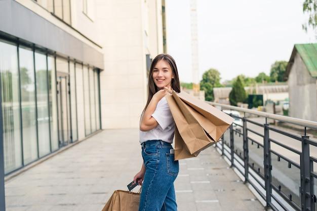 デイショッピングを楽しんでいます。ショッピングバッグを持って通りを歩きながら笑っている若い女性の全長