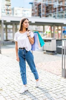 一日の買い物を楽しんでいます。買い物袋を押しながら通りを歩きながら笑顔の若い女性の完全な長さ