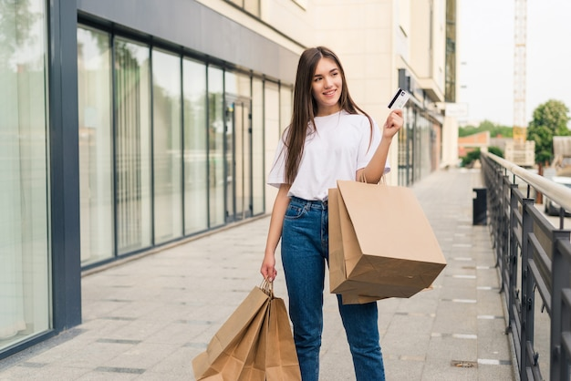 Enjoying day shopping. full length of young woman holding shopping bags and smiling while walking along the street