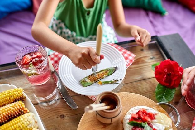 夕食を楽しむ子供女の子がナイフとフォークで食べる、夕食のテーブル、前菜のバラエティサービング