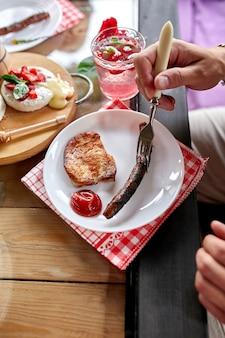 Наслаждаясь ужином, человек ест мясо, обеденный стол, разнообразные закуски, подаваемые на стол на открытом воздухе.