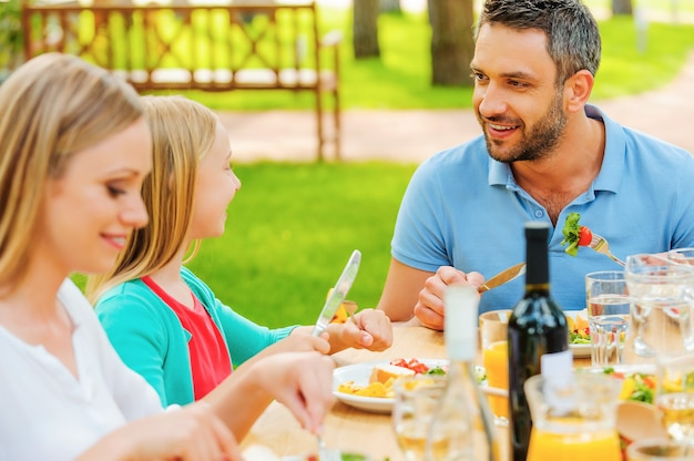 Enjoying dinner together. happy family enjoying meal together while sitting at the dining table outdoors