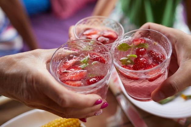 가족 또는 친구와 함께 저녁 식사를 즐기고, 딸기 레모네이드로 건배 건배, 탑 뷰 디너 테이블. 프리미엄 사진