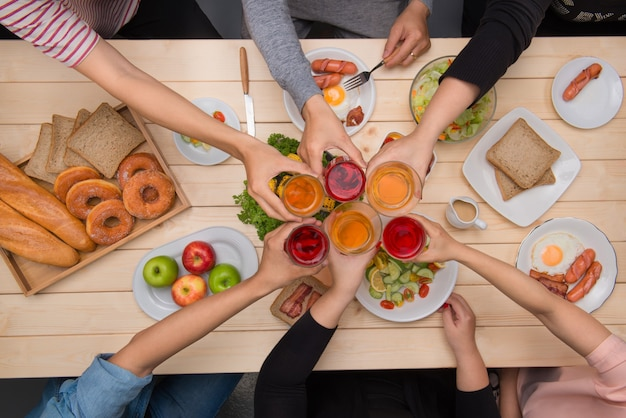Enjoying dinner with friends.  top view of group of people having dinner together while sitting at wooden table