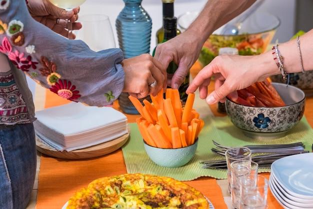 友達と夕食を楽しんでいます。素朴な木製のテーブルに座って一緒に夕食を食べている人々のグループの上面図-ニンジンを取る