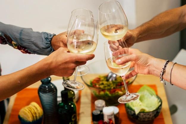 友達と夕食を楽しんでいます。素朴な木製のテーブルに座って一緒に夕食を食べている人々のグループの上面図-つる