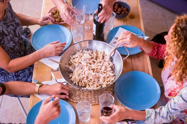 友達と夕食を楽しんでいます。素朴な木製のテーブルに座って一緒に夕食を食べている人々のグループの上面図。素敵なナイトライフやランチタイムにぴったりのワインとイタリアンパスタ。大人と若い