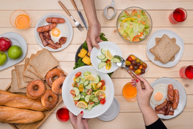 친구들과 저녁 식사를 즐기고 있습니다. 나무 테이블에 앉아있는 동안 함께 저녁 식사를하는 사람들의 그룹의 상위 뷰