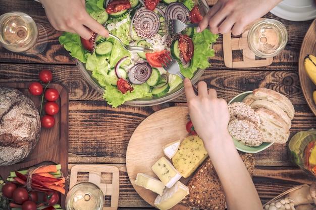 友達とディナーを楽しんでいます。一緒に夕食を食べている人々のグループのトップビュー
