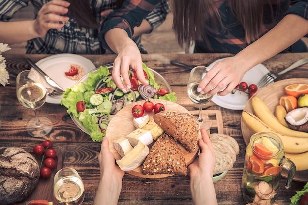 友達とディナーを楽しんでいます。素朴な木製のテーブル、お祝いの概念、健康的な家庭料理に座って、一緒に食事をする人々のグループの平面図
