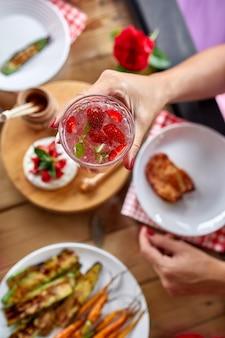 夕食の女性が家でパーティーの屋外のテーブルで提供するレモネード、夕食のテーブル、前菜の多様性を食べ、飲むのを楽しんでいます。
