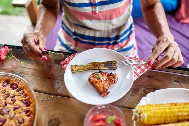 ナイフとフォーク、夕食のテーブル、前菜のバラエティサービングで食べる夕食の女性を楽しんでいます