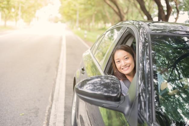 Красивая женщина азии улыбается и enjoying.driving автомобиль на дороге для путешествия