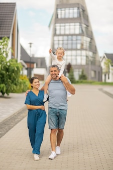 Наслаждаемся вечерней прогулкой. счастливая веселая семья чувствует себя хорошо, наслаждаясь вечерней прогулкой в коттеджном городке